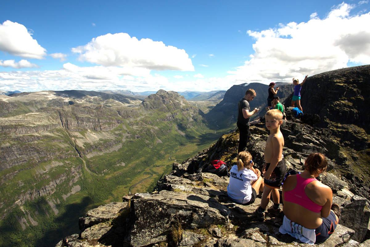 HVA HVIS DETTE GÅR GALT? Bildet er fra en folksom dag på toppen av det bratte fjellet Innerdalstårnet på Nordmøre, sommeren 2014. Hvem sitt ansvar er det hvis disse folkene faller ned og skader seg? Foto: Tore Meirik