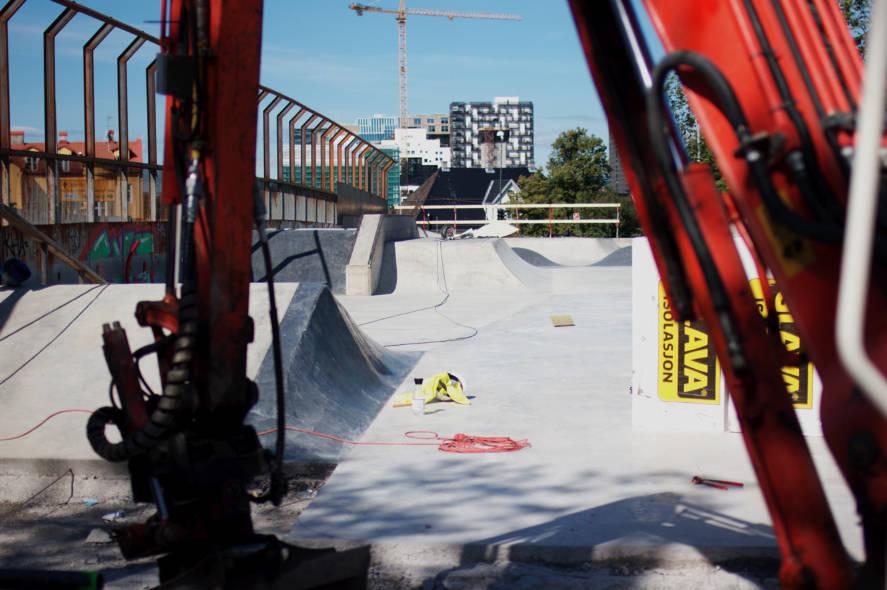 Gravemaskin, glava og ny betongpark.