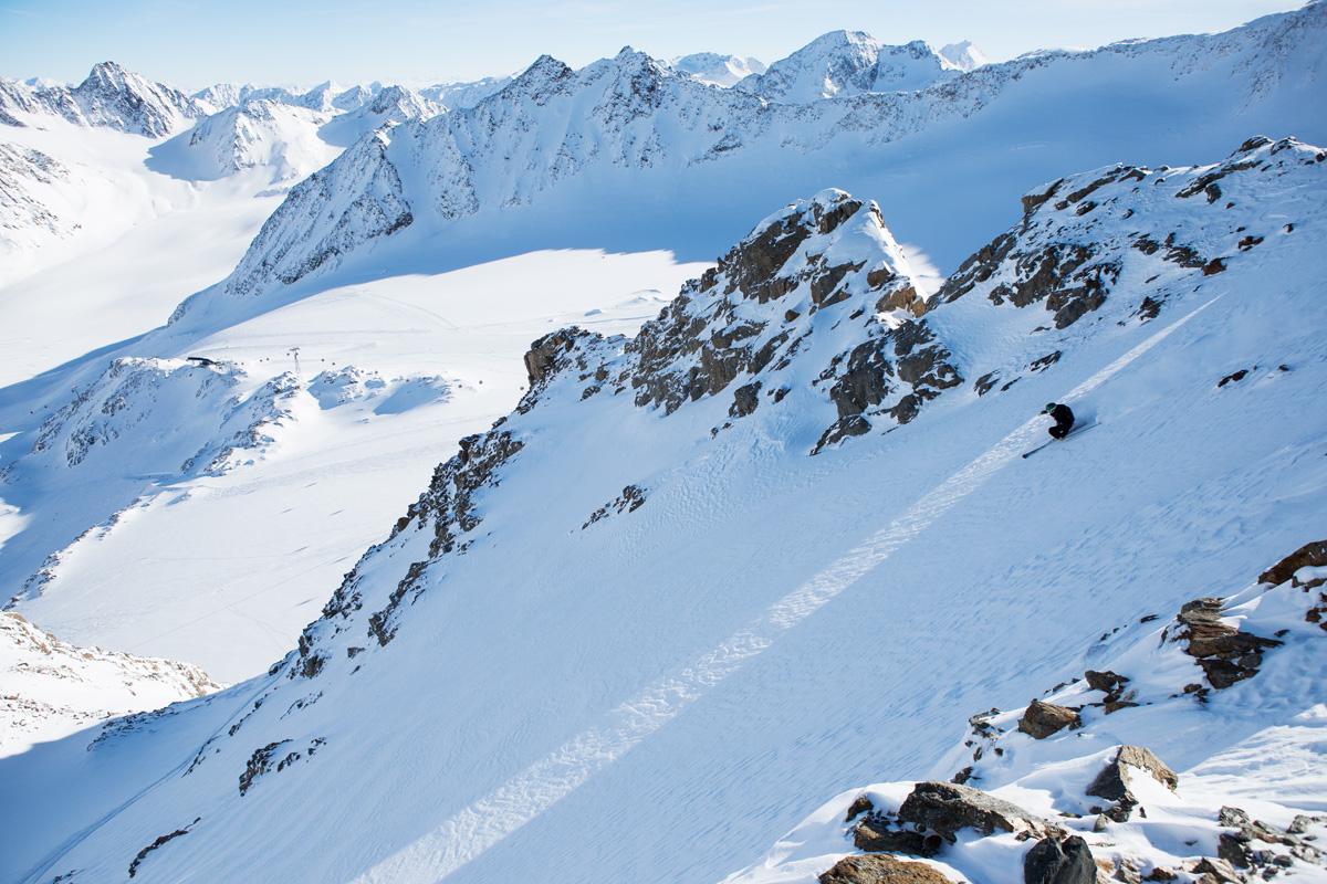 PÅ RYGG: I deilig snø setter Magnus Tveito fart fra ryggen under heiswiren og ned mot breen med Østerrikes høyestliggende alpinløyper under. Foto: Tore Meirik