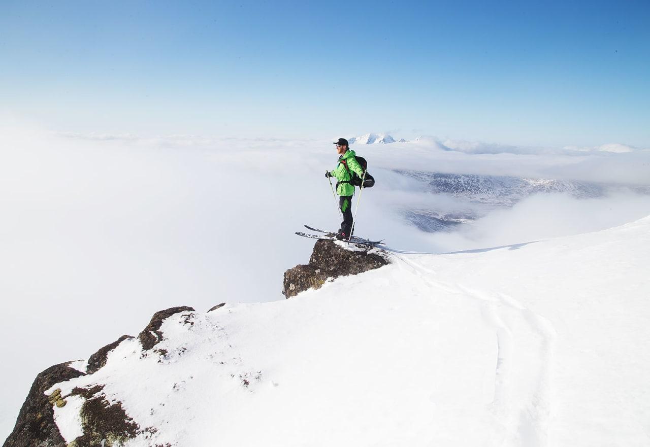 David Underland nyter utsikten når skyene sprekker opp på toppen av Justatind. Foto: Nils-Erik Bjørholt