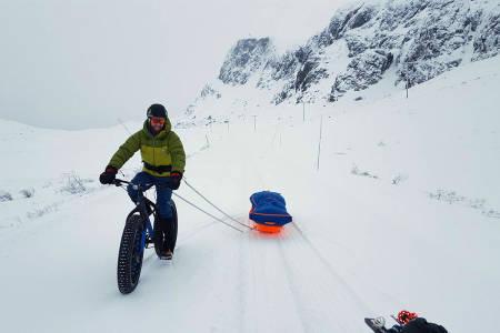 TIL TOPPS: Andreas Dahl på sykkel med skiene på slep. Foto: Privat