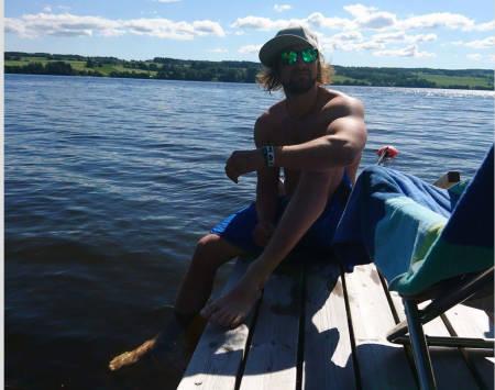 SOMMER-DENNIS: Dennis Risvoll slapper av ved vannet hjemme i Vågå.