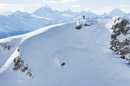 MIDT I SMØRØYET: Trygve Sande setter fart i toppen av et langt run på baksiden av skisenteret i Leukerbad. I bakgrunnen ses noen av Alpenes høyeste og mest ikoniske fjell. Weisshorn (4 506 moh), Zinal Rothorn (4 221 moh), Matterhorn (4 478 moh) og Dent Blanche (4 357 moh) ses bak Kilian Roten. Foto: Tore Meirik