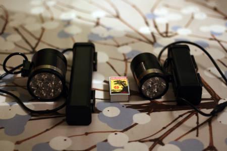 STOR OG KRAFTIG: Moonlights Bright as Day 4000 til venstre og 2000-versjonen til høyre, begge med batteriene. Fyrstikkeska i midten viser størrelsesforholdet. Foto: Tore Meirik