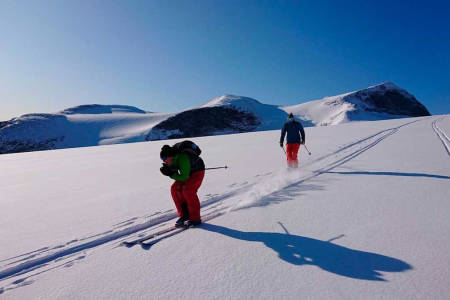 FARTSGLADE: Frode Skjeldal og Rune Røsten har tatt fri fra treningssamlingen til Kjelsås alpin og sporer nysnøen over Styggebreen med Galdhøpiggen i bakgrunnen.