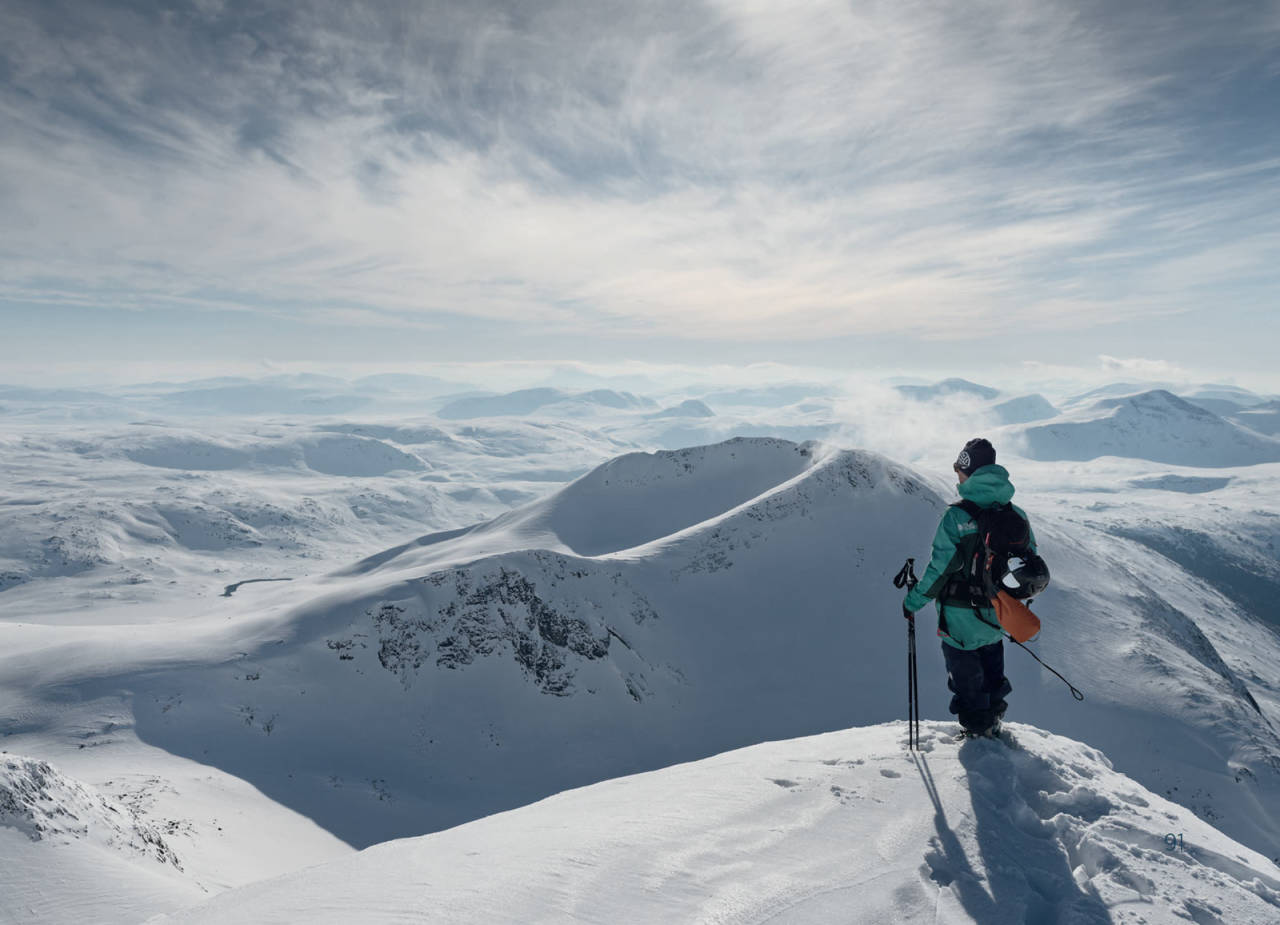 Kristoffer Turdell står på toppen av Ippočohkka og ser over mot toppen av Durmålstinden. Foto: Anna Öhlund / Toppturer rundt Narvik.