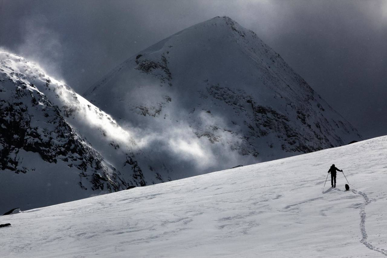Lars Thulin og hunden Coffee på tur, med Gahperčohkkas mektige nordvegg i bakgrunnen. Foto: Nicklas Blom / Toppturer rundt Narvik.