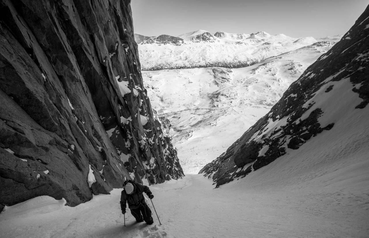 Tobias Jakobsson på tur opp i en av de bratte rennene på Lappviktinden. Toppene i Skjomdalen og ved Lossihyttene vises i bakgrunnen. Foto: Fredrik Bengtsson / Toppturer rundt Narvik.