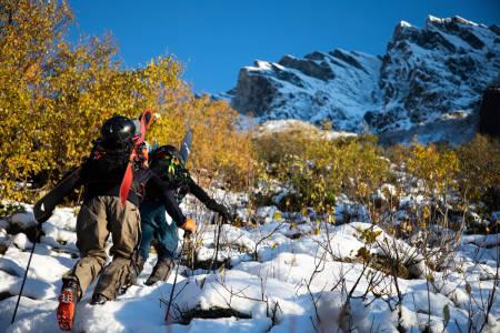 På vei opp med gult løv på trærne, syltynt snølag på steinene og tøffe fjell i sikte.