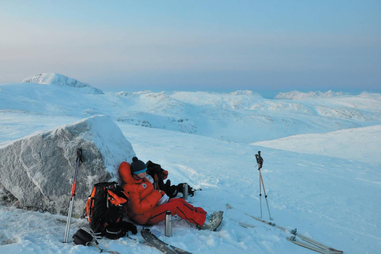 Heidi Berg nyter tekoppen, matpakka og ei stille stund på Skarlitinden. Foto: Espen Nordahl. / Toppturer i Troms.