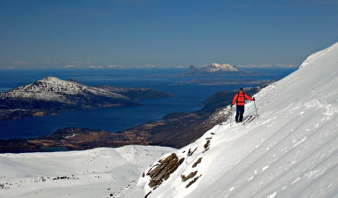 Christian Kjeldal i vestflanken på Sautinden. Øya Landegode i bakgrunnen med Lofotveggen i horisonten. Foto: Eirik Grimstad. / Toppturer rundt Bodø.