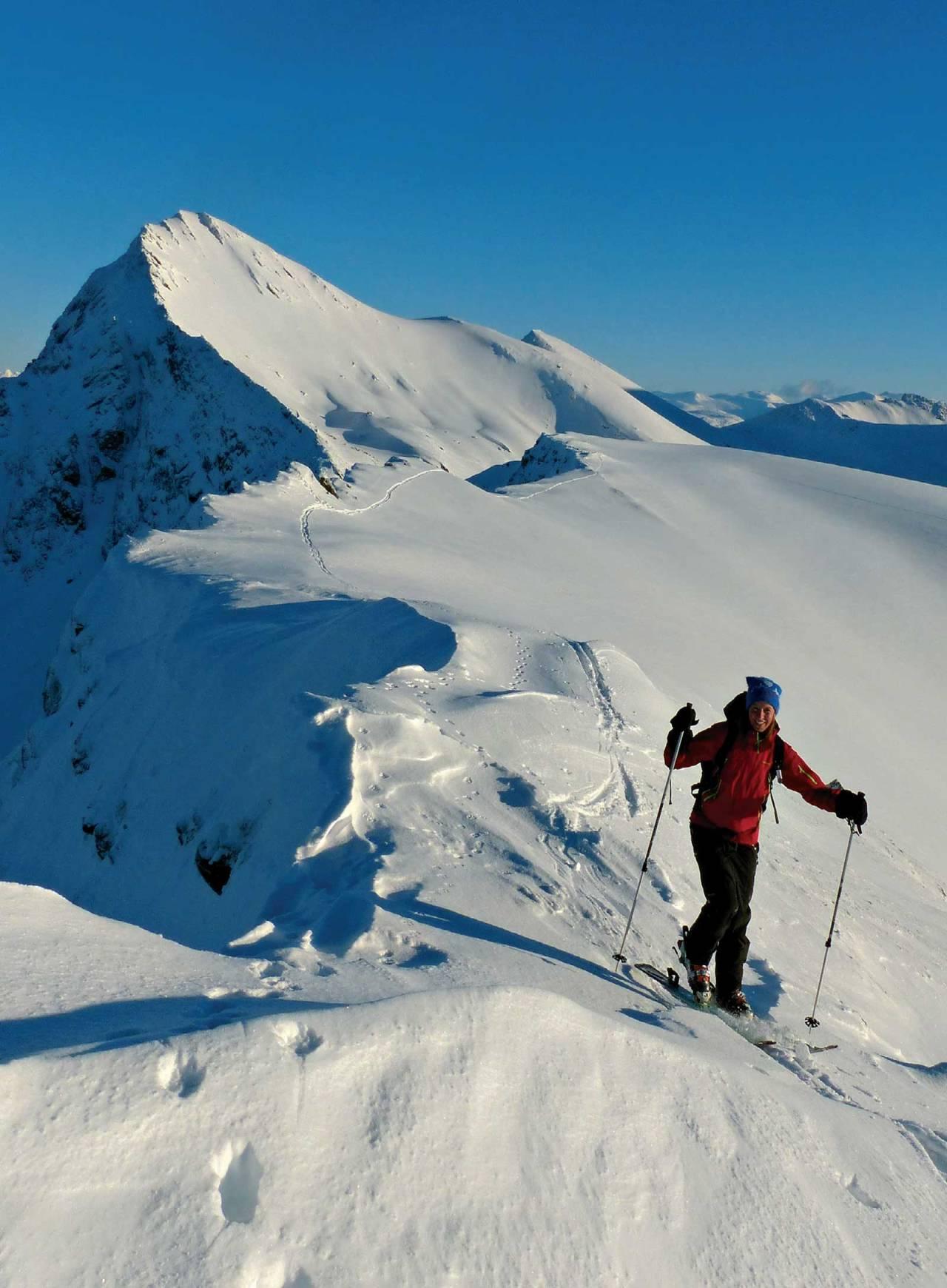 Sydvestflanken på Digra dominerer bakgrunnen idet Gøril Stordal topper ut på Spannstinden. Tverrfjellet stikker så vidt opp og har skygge i nedre halvdel av sydvestflanken. Foto: Torgeir Kjus. / Toppturer rundt Bodø.