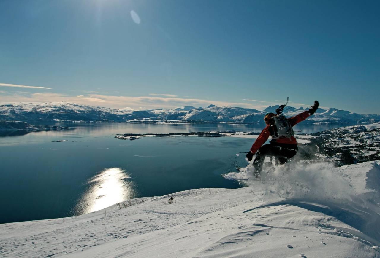 Ingunn Limstrand på tur ned mot Sagelva med Saltfjorden i stilla og Børvasstindan i bakgrunnen til høyre. Foto: Jan Erik Paulsen. / Toppturer rundt Bodø.
