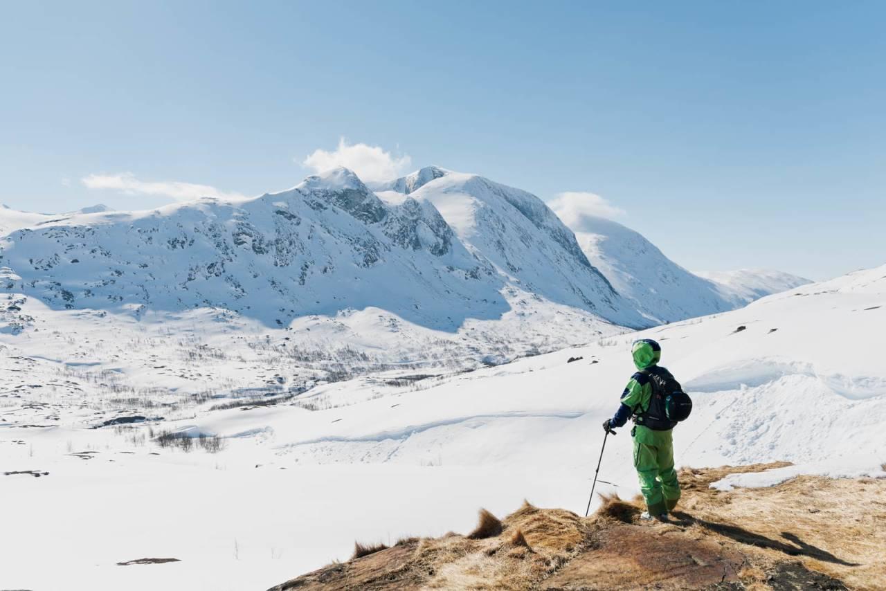 Robin Klemo beundrer utsikten fra gressflekken utenfor Lossihyttene, mot Ippočohkka og Durmålstinden. Foto: Anna Öhlund / Toppturer rundt Narvik.