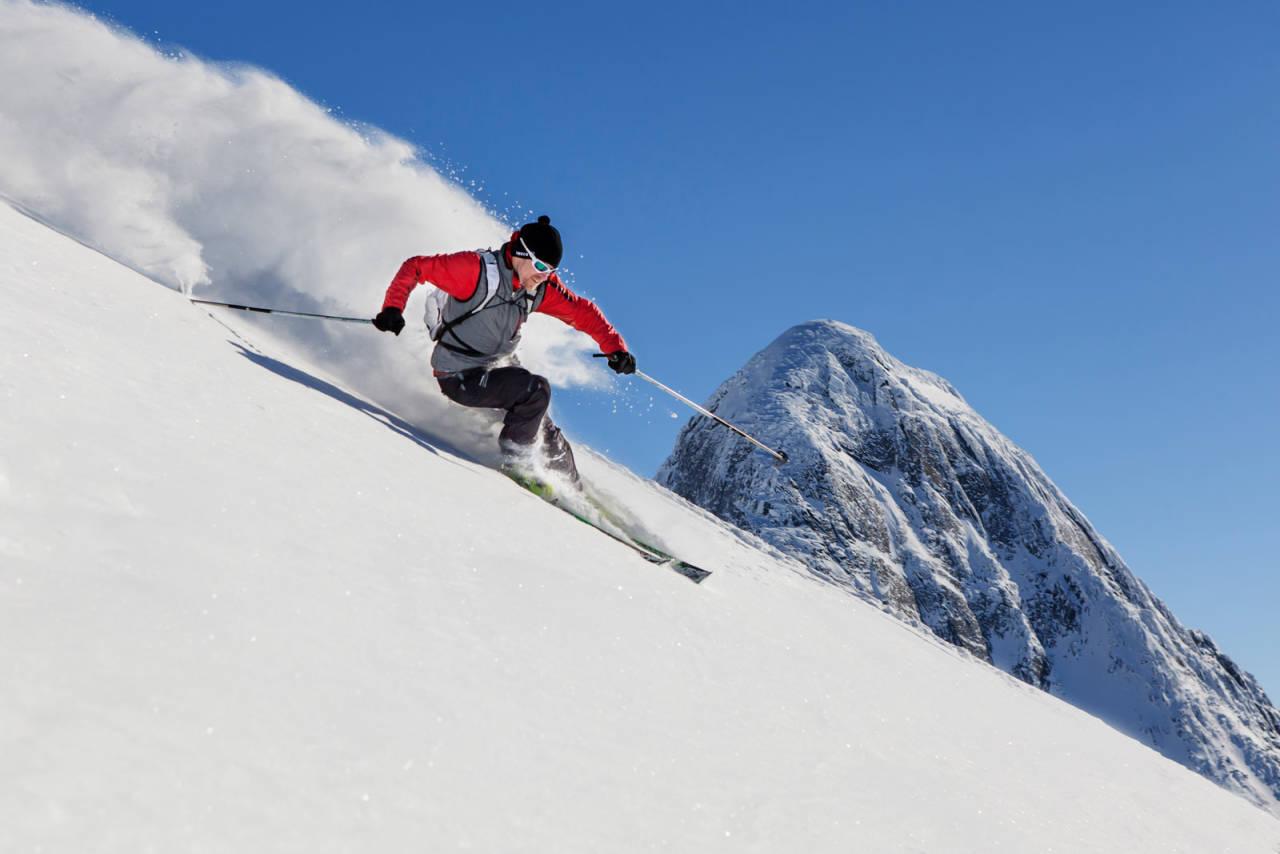 Mikael af Ekenstam på tynne ski på tur ned fra Rienatčohkkas sørtopp. I bakgrunnen reiser Huinnarčohkka seg. Foto: Jan-Arne Pettersen / Toppturer rundt Narvik.