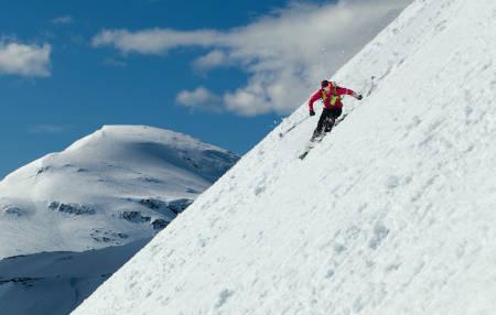 Nedkjøring fra Stortinden ned mot Grasdalen, med Læigastinden i bakgrunnen. Mikael af Ekenstam prøver å unngå våte snøskred. Foto: Jan Arne Pettersen / Toppturer rundt Narvik.