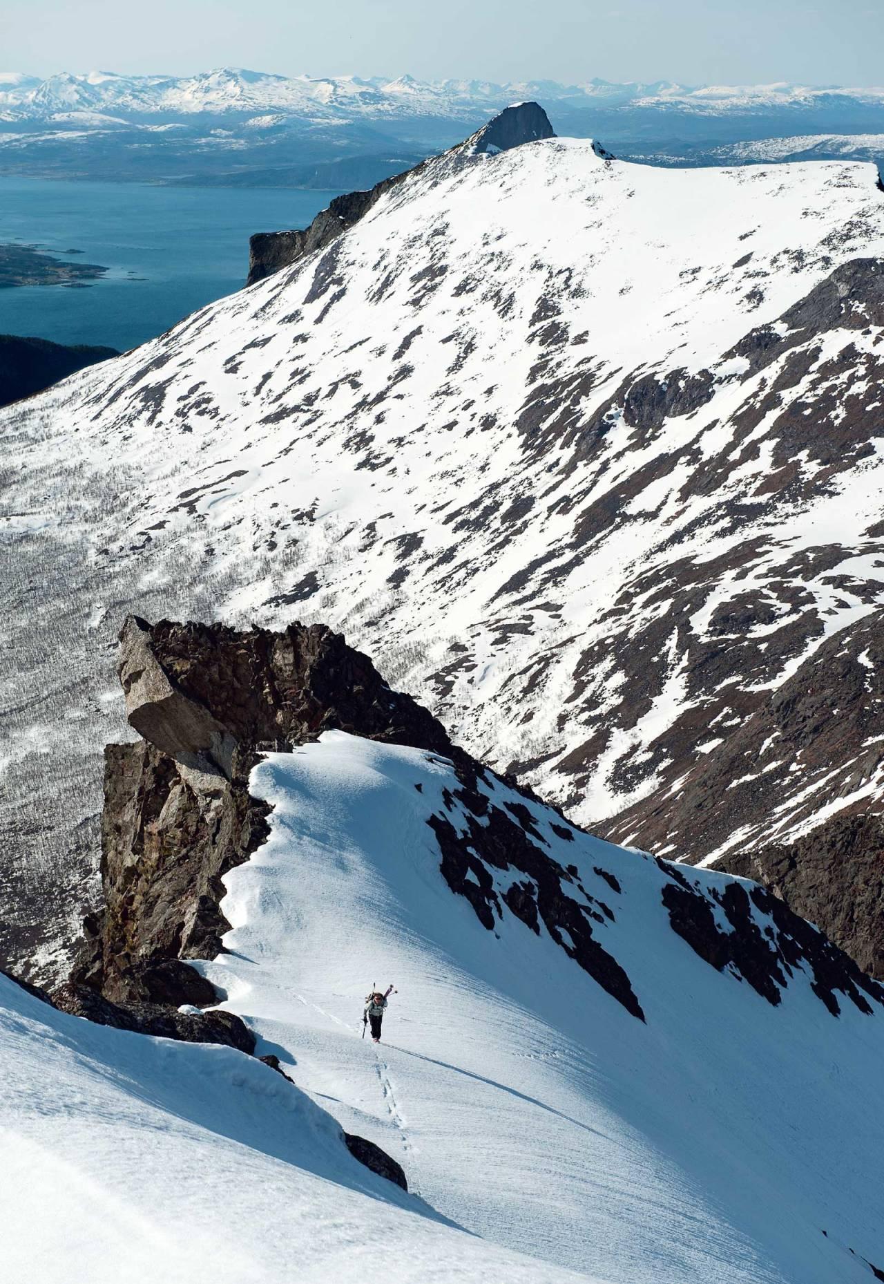 Mikael af Ekenstam på tur opp mot Klubbviktinden. I bakgrunnen vises Rånkeipen og eggen over Boazovárri. Foto: Lars Thulin / Toppturer rundt Narvik.