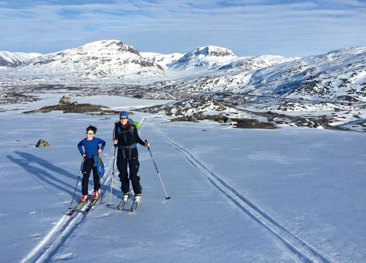 Isak Lyngvær og Trude Johnsen på tur opp mot Bjørnfjell, med Riksgränsen i bakgrunnen. Foto: Per Inge Lyngvær / Toppturer rundt Narvik.