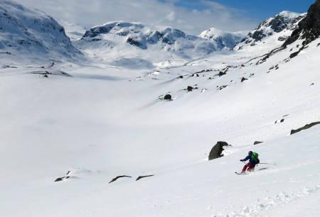 Vidar Mong koser seg på vei ned sørrenna på Store Nup. I horisonten ser du Sveigen til venstre, Dyrskardnuten rett frem og p1586 til venstre. / Fra Toppturer i Sørvest.