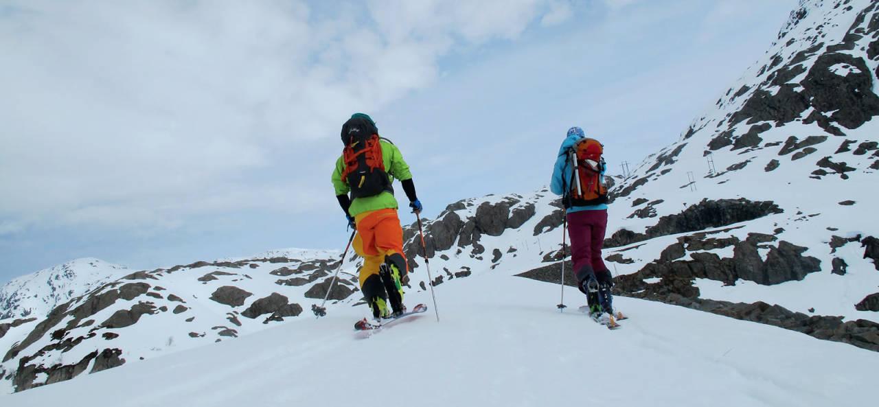 Rino R. Berg og Ida Sollie er på vei over demningen. Målet er Bukkanuten. Anmarsjen blir litt lengre  når man er ivrigere enn snøsmeltingen. Foto: Trygve Studsvik