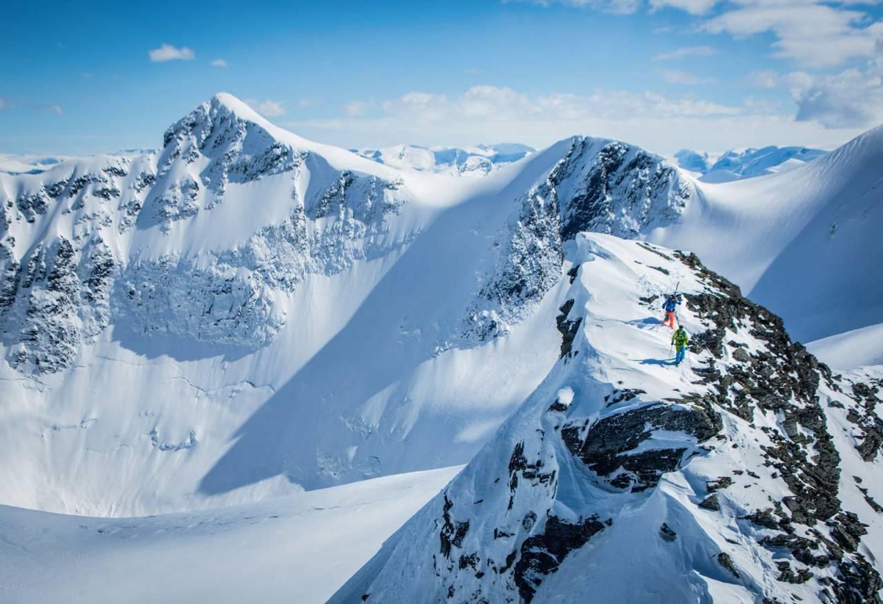 Skiløparar klyv opp mot Bjørkehornet på jakt etter ei spektakulær nedkøyring. Rokkekjerringa kneisar i bakgrunnen. Storhornet ligg opp til høgre, utanfor biletet. Foto: Håvard Myklebust.