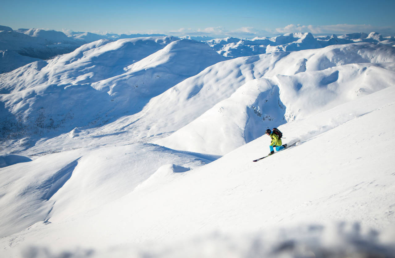 Telemarksvingar i «snilt» skiterreng ned hovudflanken. Vi ser korleis Nordfjordfjella i bakgrunnen er typisk meir avrunda i forma enn dei kvasse Sunnmørsalpane. Foto: Håvard Myklebust.
