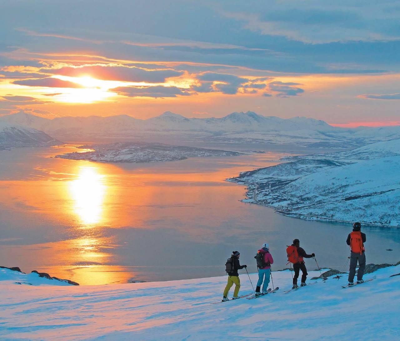 Fornøyde skredkursdeltakere nyer årets første solstråler over Tromsøya.  Foto: Espen Nordahl. / Toppturer i Troms.
