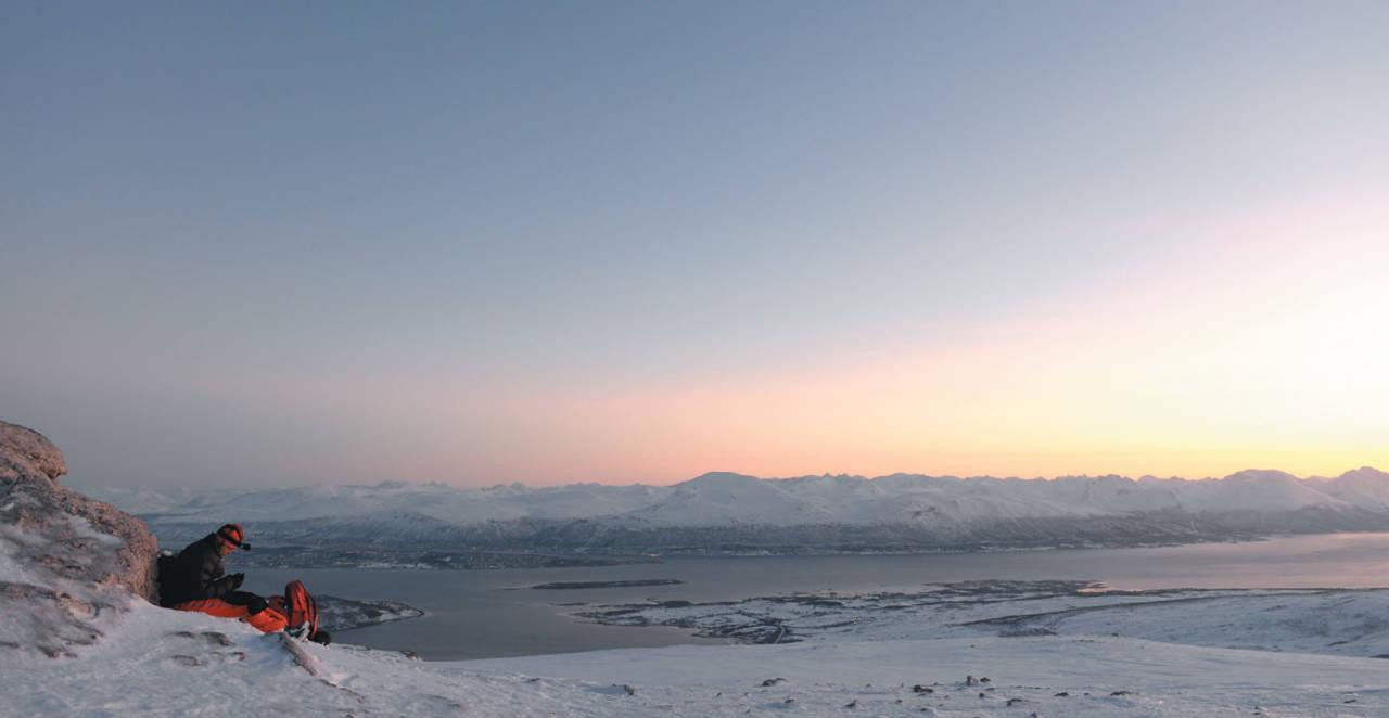Heidi Berg nyter en stille magisk januarstund ved varden på Lille Blåmannen. Foto: Espen Nordahl. / Toppturer i Troms.