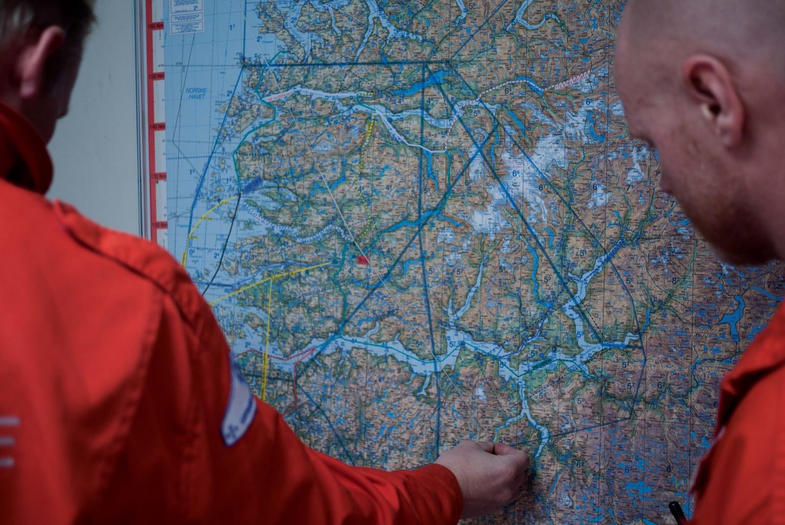 AVSTAND: Pilot Geir Svevad (t.v.) og redningsmann Kjetil Leknes ser på avstander fra basen i Førde. Tråden er festet til et lodd. Når man drar i tråden, føres loddet opp en skala der man ser distansen. Foto: Henning Reinton