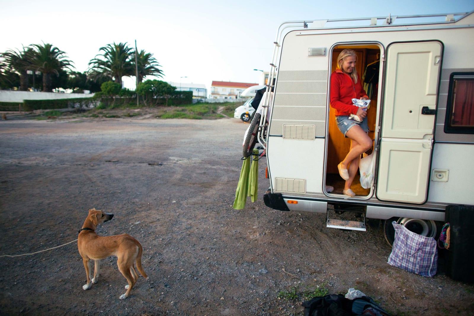 """PÅ GJENNOMREISE: Hunden fra en av de andre campingbilene på parkeringsplassen i Sagres vil gjerne hilse på Anna Sara Fjeld. Østfoldjenta og bilen """"Helga"""" har vært noen måneder på tur i Europa for å sykle, klatre og surfe. Algarve med sine fine strender og varmere vann var et naturlig valg når det skulle surfes. Foto: Thomas Kleiven"""