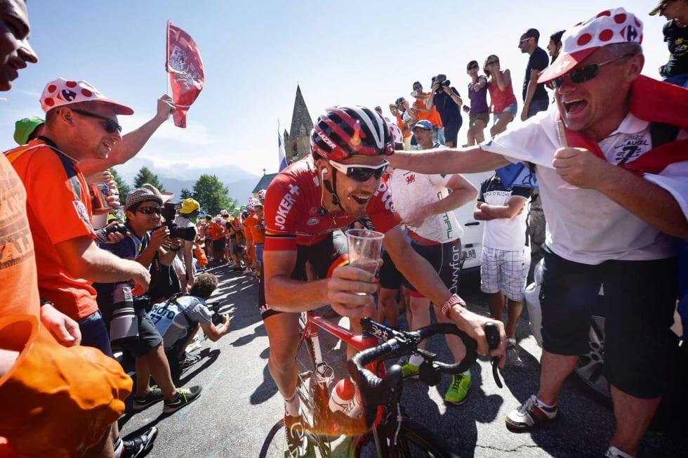 PUBLIKUMSHELT: Adam Hansen vet å by på seg selv under sykkelritt. Når han er ferdig som hjelperytter tar han seg gjerne en øl sammen med fansen. Foto. Cor Vos.