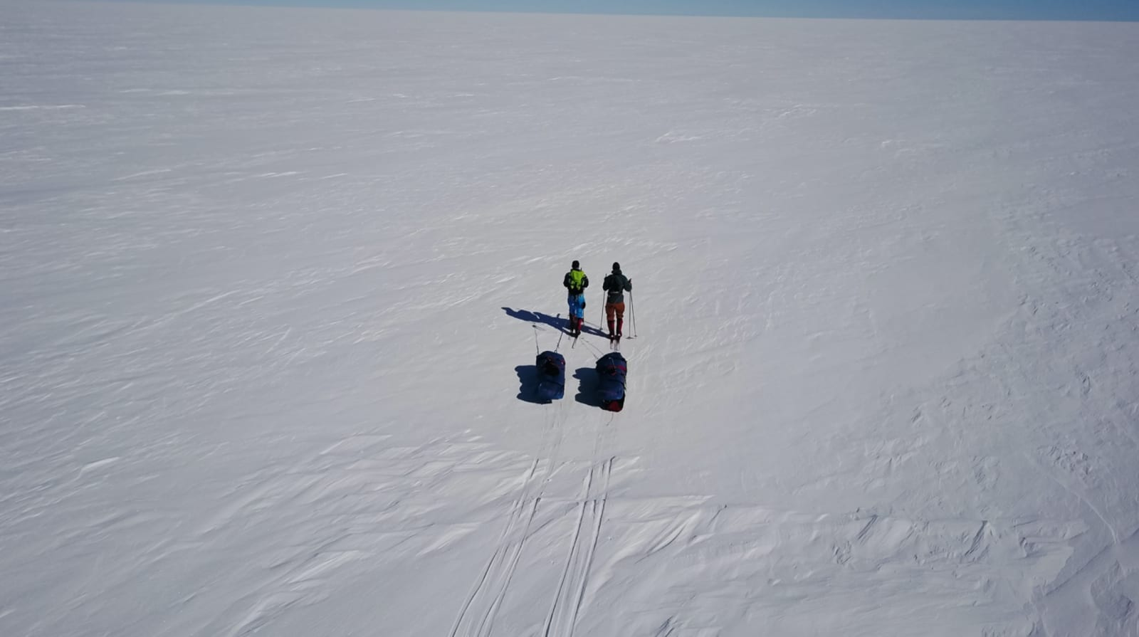PÅ DET HVITE LERRETET: I godt driv over Grønlandsisen, på en av svært få finværsdager. Imidlertid er det finværsdagene som gir de kaldeste nettene, noe som gjorde at man virkelig satte pris på solen på dagtid.
