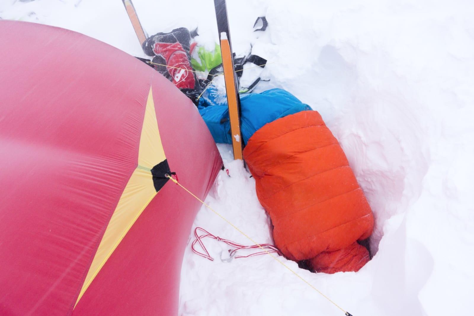 SIKRING PÅGÅR: Stormsikring innebærer ofte sikring av teltet med tau og isskruer. For å komme ned til ren is, trenger vi som oftest ikke grave mer enn 1-1,5 meter.
