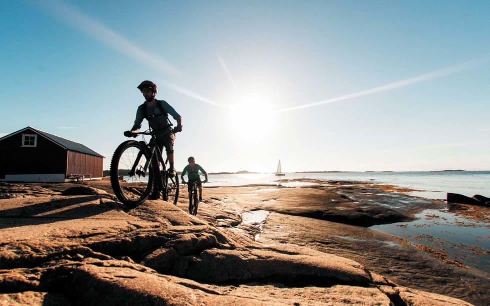 SOMMERFRI: Thomas B. Svendsen og Morgan Bakken sykler med morgensola i ryggen utenfor Kragerø.
