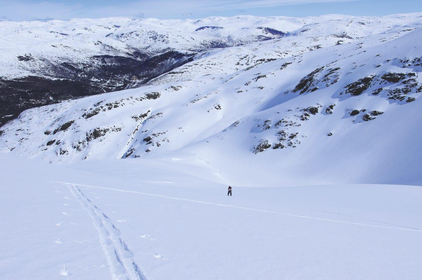 NY MOTBAKKE: Man føler seg liten i mektig natur. Her er May Helen på vei mot Seldalsnuten, turens andre topp. I fjellsiden bak kan man skimte sporene våre etter nedkjøring fra Olsskavlen.