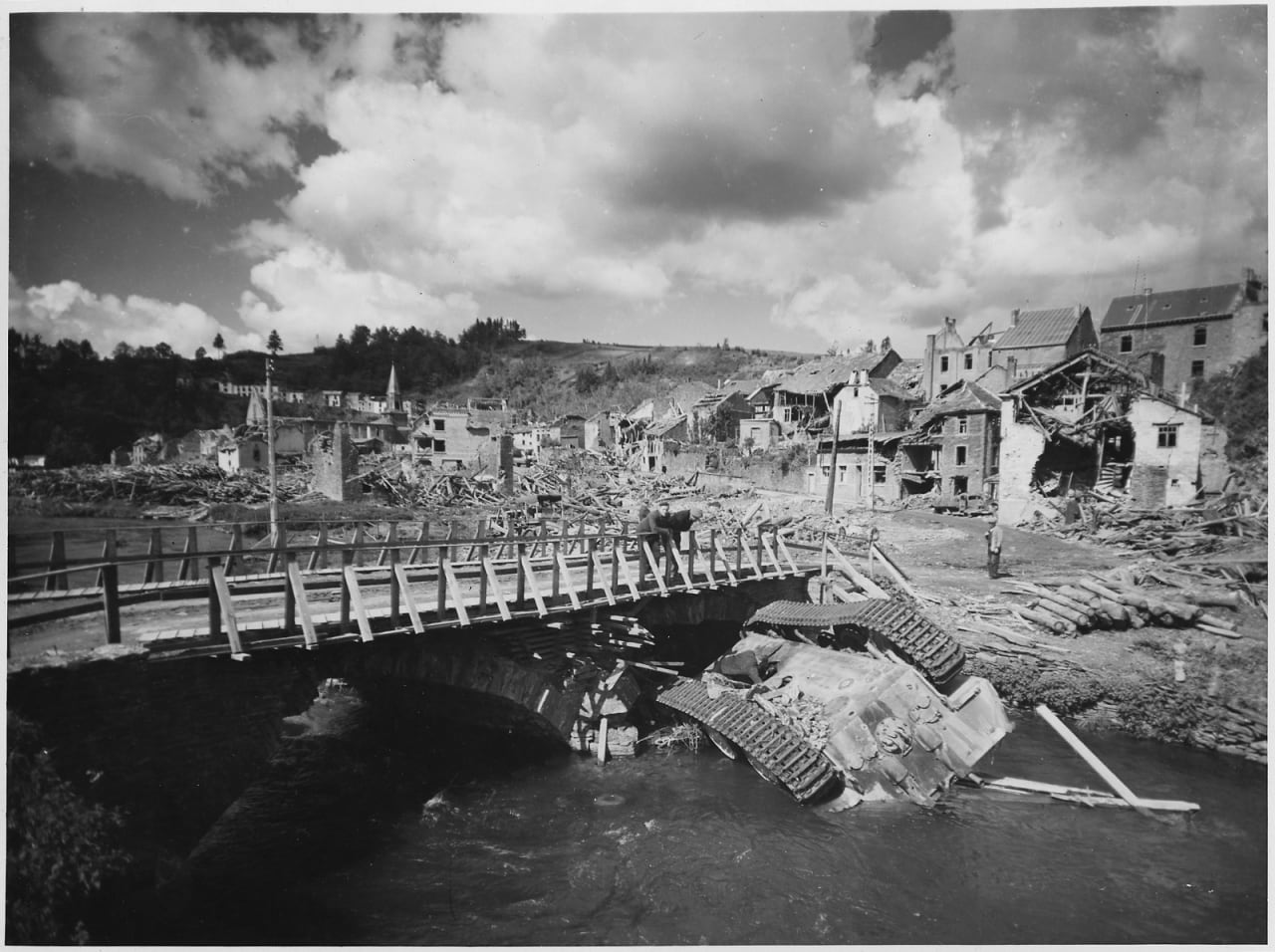 An_overturned_German_tank_lies_in_a_shallow_stream_alongside_a_rebuilt_bridge_in_war-ravaged_Houffalizo,_Belgium._-_NARA_-_196224