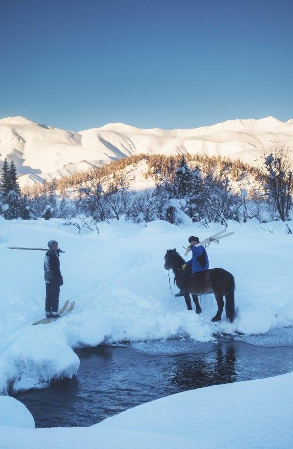 HEST OG SKI: Serik møter en av naboene på vei hjem fra jaktturen. Både hesten og skiene er livsviktig i samfunn som Akhorm. Bilde: Erlend Sande