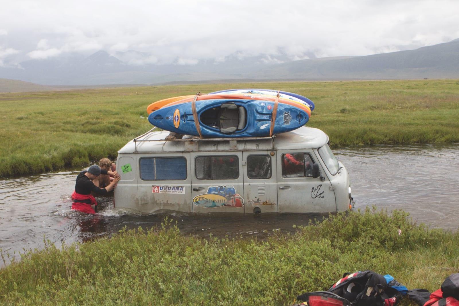 HELL I UHELL: Til tross for at Uaziken tok kvelden i et dypt elvehull, fikk teamet dytta og dratt bilen ut av vannhullet. Bilde: Mariann Sæther