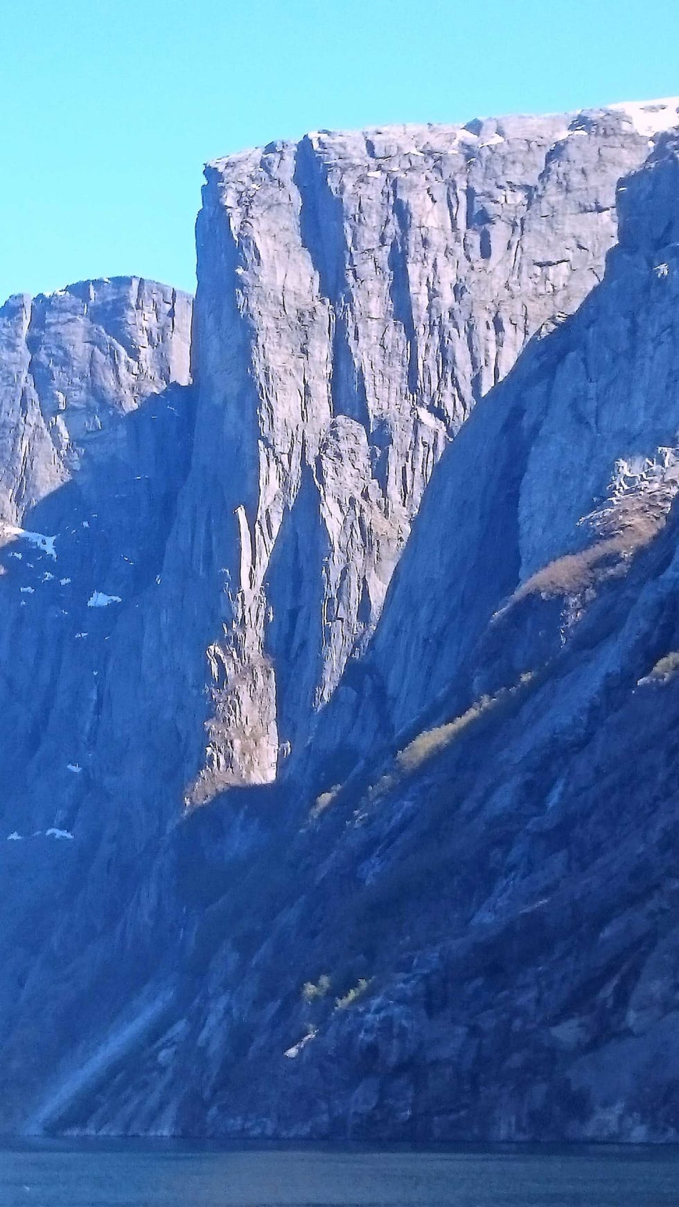 Ulykker: Frontveggen på Kjerag er snaut 900 høydemeter og har en lett synlig gylden plate i toppen hvor ruta Skjoldet går. Til høyre og nedenfor denne er en markert pilar som danner skillet mellom lys og skygge på bildet, og rundt foten av denne har det skjedd minst to fall-ulykker med beinbrudd. Foto: Sindre Bø