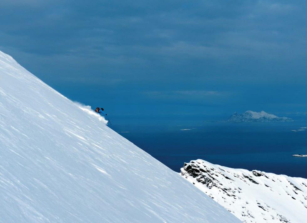 Anders Dahle setter utfor den fantastiske østflanken på Isvasstinden. Lofotveggen kan anes i horisont. Foto: Torgeir Kjus. / Toppturer rundt Bodø.