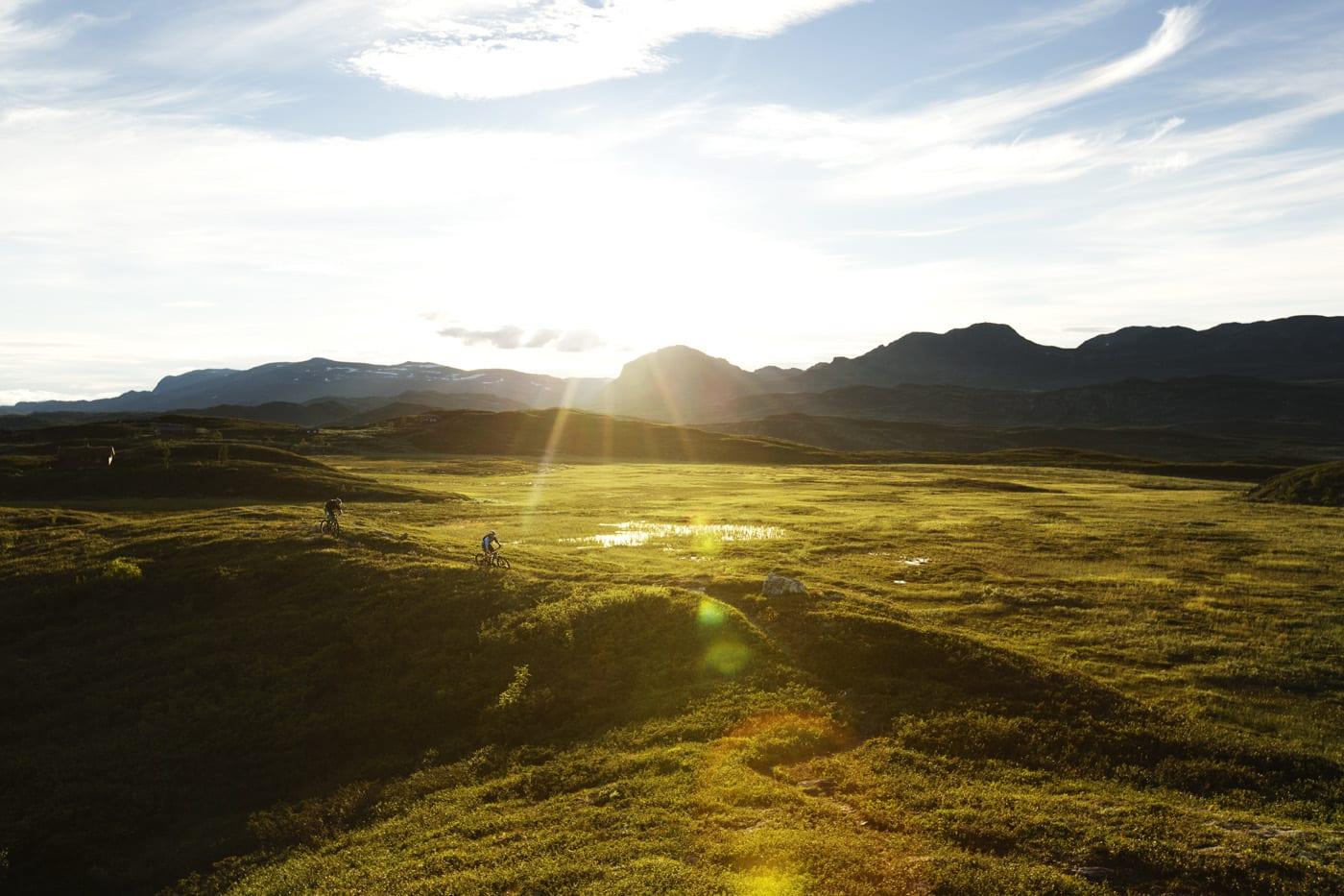 SYKLISTER I SOLNEDGANG: Bård Sturla Stokke og Ådne Kvammen får med seg de siste solstrålene over Veali, Ål.