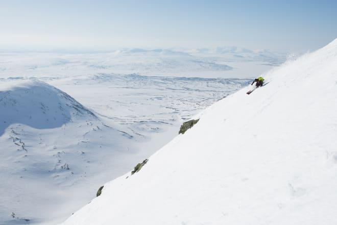 MED NORGE I SIKTE: Den vestvendte nedkjøringen på den norske siden av Storsylen er lang, jevn og deilig. Særlig i myk vårsløsj. Robert Pallin Aaring setter en fin ettermiddagssving på den høyeste fjellet i svenskenes favoritt-toppturområde. Foto: Tore Meirik