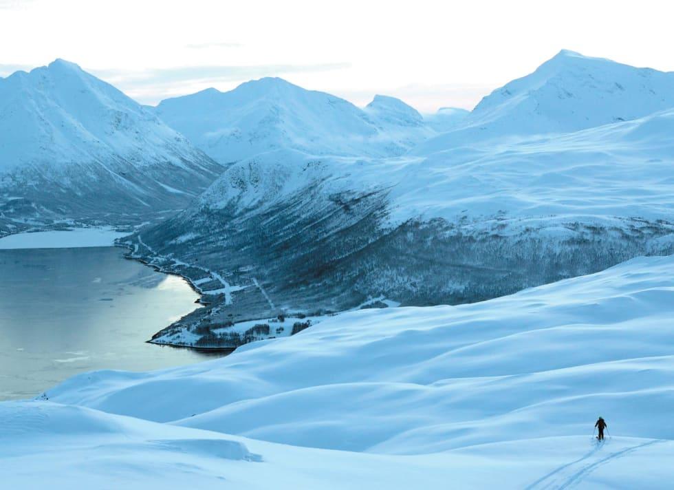 Svein Mortensen nyter kulden og et magisk lys på baksiden av Tromsdalstinden med utsikt mot Ramfjorden. Foto: Espen Nordahl. / Toppturer i Troms.