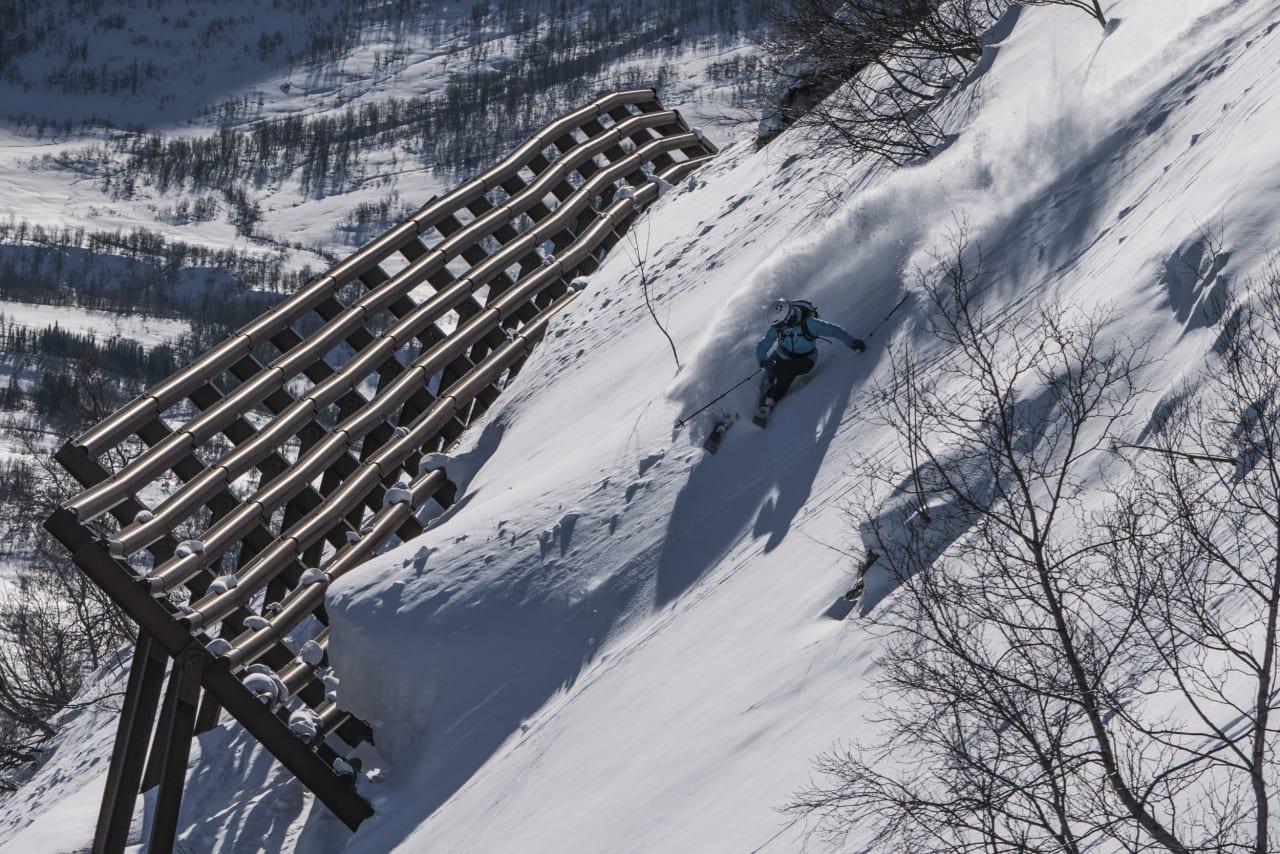 BYNÆRT: Den smålegendariske frikjøreren Eric Hjorleifson kjører i renna på toppen av Hovsnebba like overfor Sunndalsøra. I bakgrunnen ser du foten til Storkalkinn, Nord-Europas høyeste kystfjell. Foto: Mattias Fredriksson.