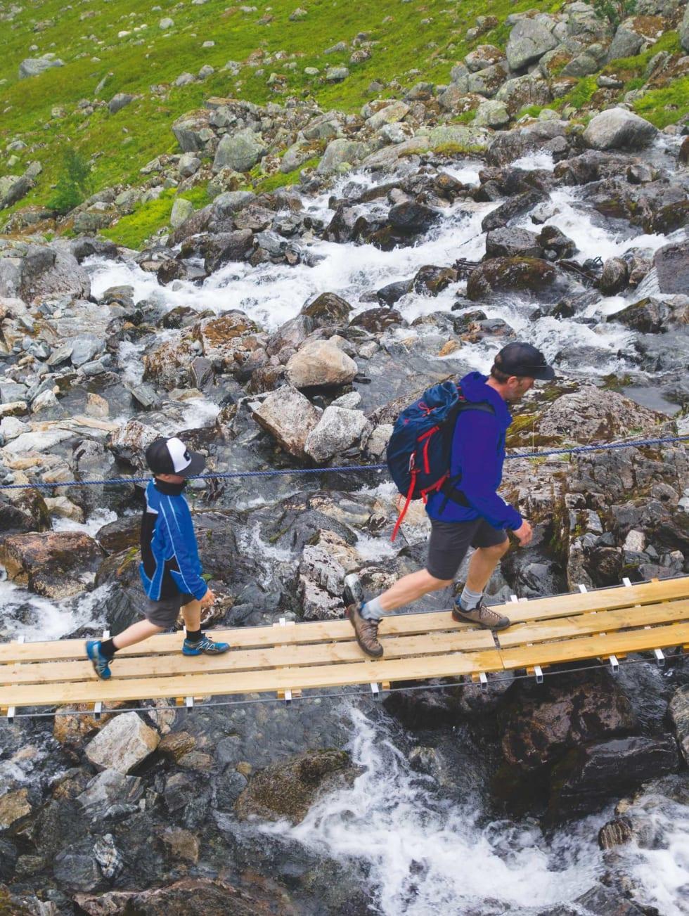 HVEM TRAMPER: Hjalmar (7) og Jørgen Aamot på vei over elva innerst i Øvredalen. Foto: Erlend Sande