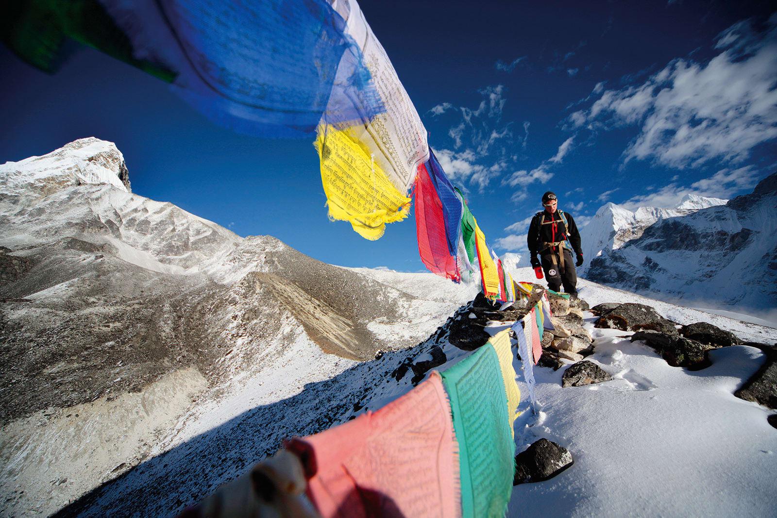 Flaggdag: Buddhistiske bønneflagg blafrer forsiktig, og sender sine bønner ut med vinden. Sondre Helgesen er på vei til Camp 1 etter akklimatiseringstur. Foto: Matti Bernitz