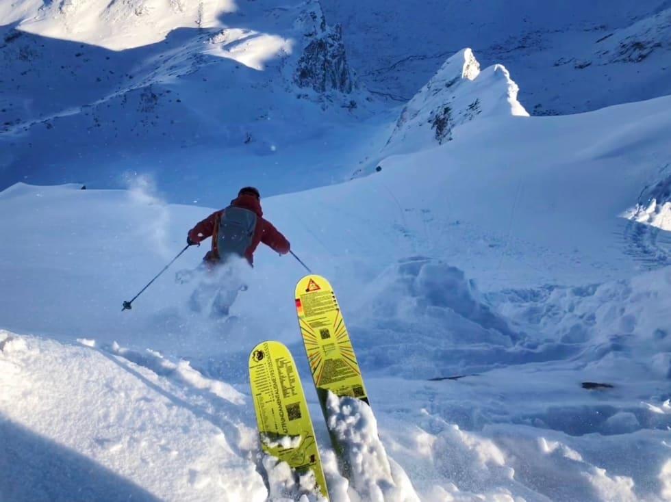 SESONGSTART: Petter Jenset setter sesongens første sving i eksponert lende og nydelig føre en meter under toppen av Store Venjetind. Bilde: Trond Stokke