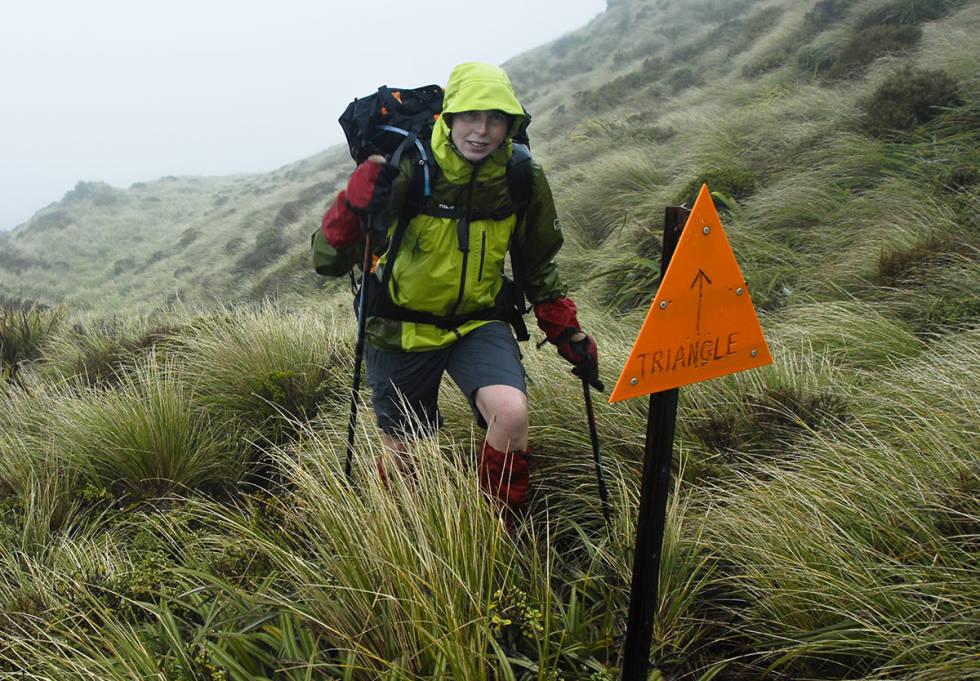 Kvinne med skalljakke, sekk og shorts i regnvær på fjellet