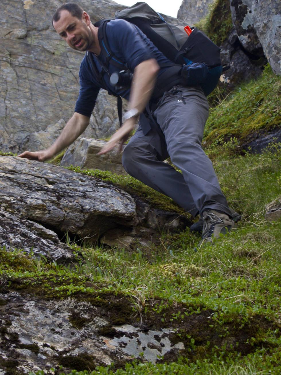 Mann går nedover i bratt fjellterreng
