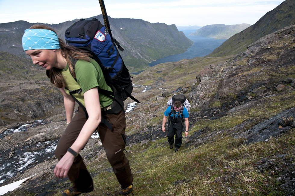 Kvinne bærer sekk i fjellet